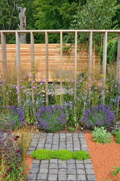 Pour l'isoler d'un voisinage gênant, ce jardin a été entouré de palissades qui occultent les alentours et décorent avec un habillage tout en bois.