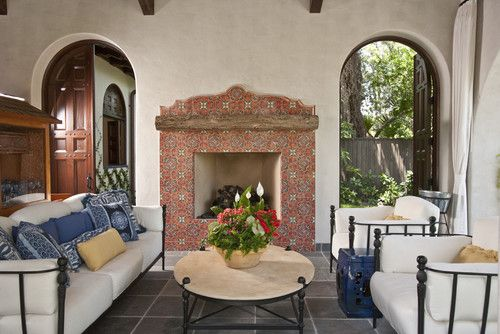 Spanish-style architecture, similar to Mediterranean style, boasts great rustic details. This fireplace features a single rustic timber as a mantel against the earthy elegance of the Mexican tile on the surround.