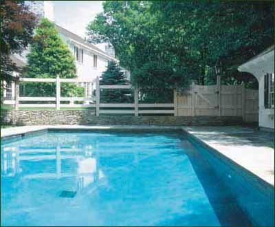 Pool Fence with Plexiglass Panels - As a departure from the norm, consider a random-width board fence with a scallop top and weathering stain. The fence incorporates plexiglass panels for a clear view from house to pool. One gate post is a lantern post.