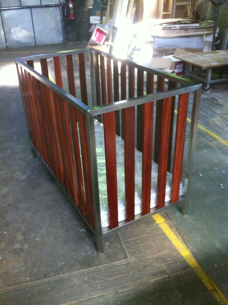 Timber and stainless steel babies cot