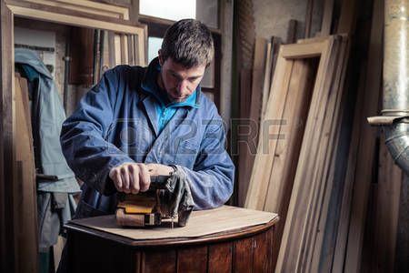 Portrait of Carpenter restoring old wooden furniture with belt sander in his Wood Shop