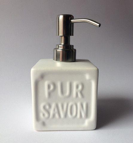 Dispenser per sapone liquido in ceramica bianca.