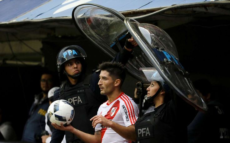The best sports pictures of 2016:     Milton Casco of River Plate is protected by police as he gets ready for a throw‐in during a Argentina league soccer match against Boca Juniors in Buenos Aires, Argentina on April 24.