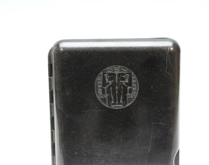 """Bakelieten sigarendoosje met afbeelding van """"de Algemeene Nederlandsche Metaalbewerkers Bond"""", ontwerp Chris van der Hoef ca. 1930. Gesigneerd met monogram ontwerper. Hoogte ca. 13,7 cm Breed ca. 10 cm."""