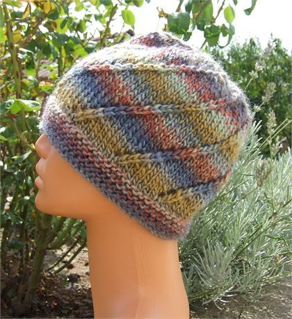 Ladies hand knitted multi colour beanie hat Spiral effect pattern with eyelet holes Knitted in self striping multi coloured soft wool in shades of blue, green, red and gold - Great casual hat Material 35 % wool - 65 % Acrylic Washable at 30 deg C (86 F) Approx size 18 diameter x 8 (44 cm x 20 cm) unstretched