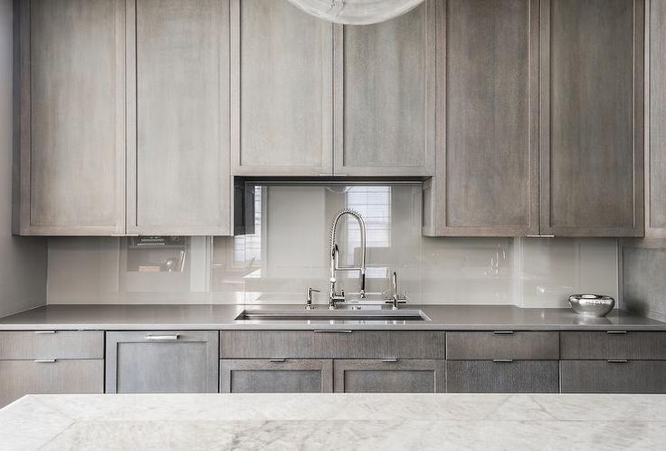 Contemporary kitchen features gray stained cabinets paired with gray quartz countertops and a lighter grey quartz backsplash. A wide stainless steel kitchen sink and a pull out faucet stands under cabinets.