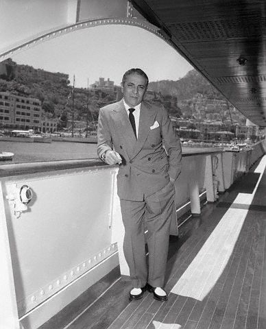 Aristotle Onassis leaning on railing of his yacht that he eventually gifted to Princess Grace Kelly and Price Rainier III of Monaco.