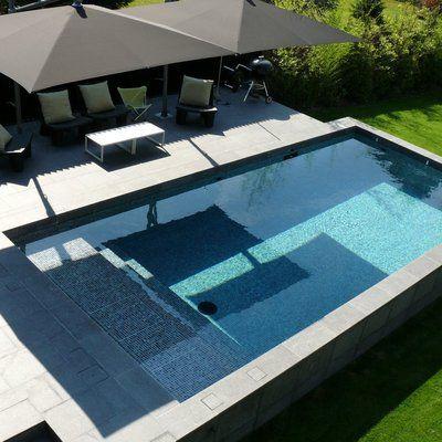 Dans le prolongement direct de la terrasse, cette piscine rectangulaire en béton armé s'inscrit comme une pièce à vivre. L'élégance du carrelage gris anthracite qui habille les parois, combiné aux plages et margelles en granit ,apporte une esthétique irréprochable. Architecte Lode Architecture. Réalisation Carré Bleu Concept