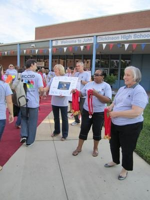 "Red Clay School District administrators lined the red carpet waiting to hand out gold medals to returning teachers Aug. 21. A few years ago, the district began a tradition by holding a themed ""District Day"" that welcomes back teachers and staff in an enthusiastic way.     This year, it was essential to choose Olympics as the theme, as district administrators, staff and special guests welcomed back busloads of teachers."