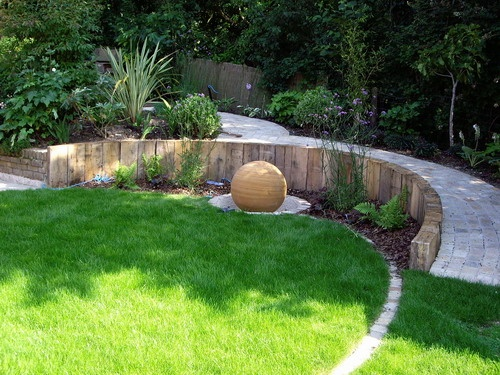 oak sleeper wall and spherical fountain emphasize circular lawn - Garden Design Circular Lawns