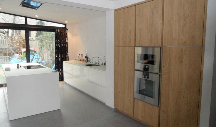 Greeploze keuken met glazen werkblad en eiken houten kasten met Gaggenau apparatuur