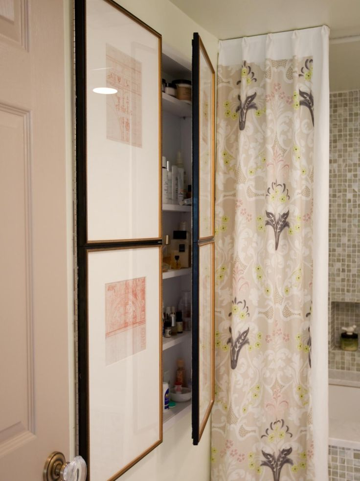 Framed Asian-style art hides the medicine cabinet in this white bathroom. A neutral patterned shower curtain with hints of green adds interest to the small space.