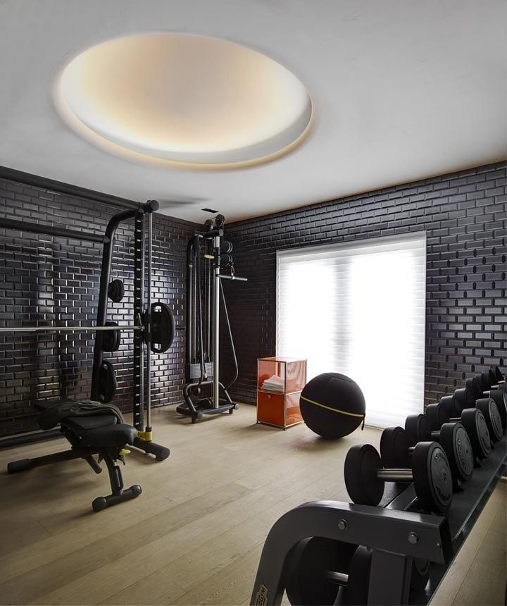 A beautiful home gym with light wood floors and black brick walls give a  calming,