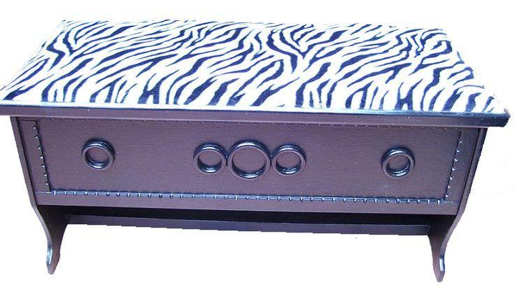 CLAF - Práctica Banca Baul Animal Print Cebra (COD 583 - Banca Baul) Fabricada en madera terciada lisa, pintada color negro, barnizada. Tapiz acolchado diseño animal print Soporta más de 120 kg. Medidas: - Largo: 82 cm - Ancho: 36 cm - Alto: 32 cm Precio: $ 28.000 www.claf.cl