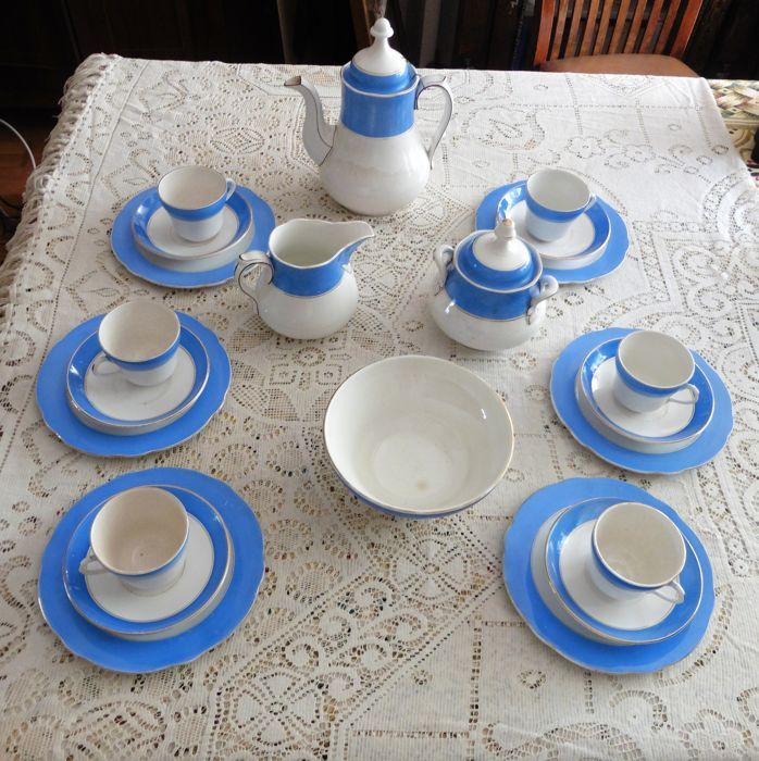 Set bestaande uit een theepot, een suikerpot, een pot van melk, 6 bekers, 6 schoteltjes, 6 platte borden en een grote kom. In wit porselein met een grote blauwe streep in het bovenste gedeelte onderstreept met een gouden draad. Hoogte van de theepot: 25 cm - grote Suikerpot met 2 handvatten in de vorm van gebladerte, hoogte: 16 cm - hoogte van de melk-pot: 11 cm - hoogte van de kom: 8 cm en diameter: 17 cm - diameter van de platen: 19.5 cm. Lion merk: Société Céramique Maestricht.