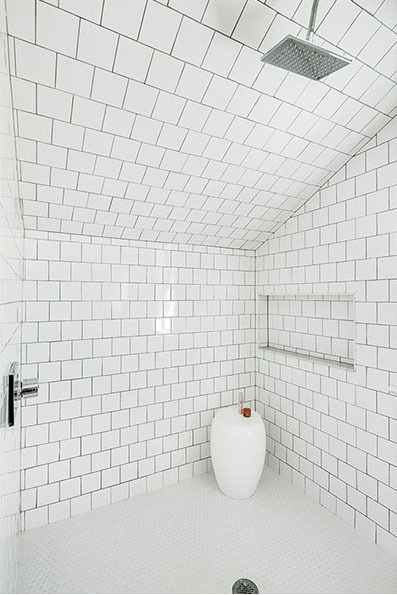 White bathroom tiles with dark grout.