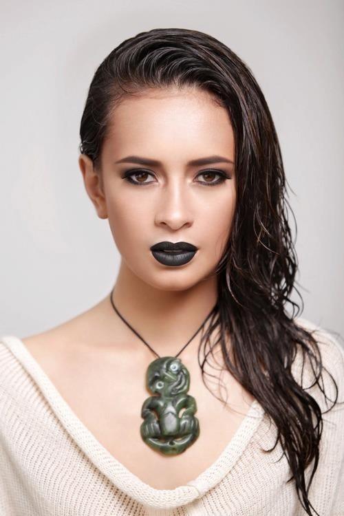 Modern Maori woman wearing a maori pendant.