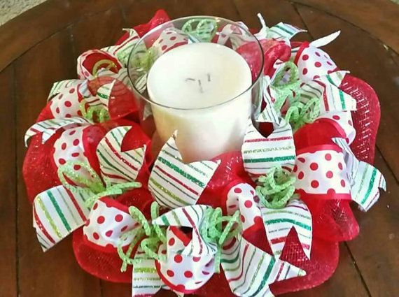 This beautiful Christmas candle ring wreath is made with a base of red deco mesh then topped with red polka dot ribbon and tied with white,