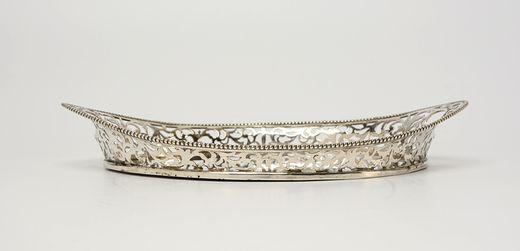 Ovaal zilveren dienblad met ajour opstaande volutenrand, parelrand en geïntegreerde handgrepen - gemerkt met Pseudo keuren - J. Postmus, Amsterdam (1905/1955) - 1909 - gehalte 0.835 - 252 gram - l. 23.5, b. 14 cm