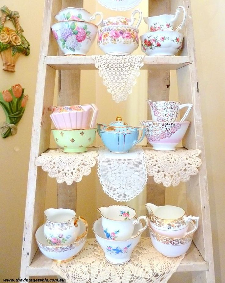 Shabby chic - vintage tea cups on doilies displayed on a chippy ladder