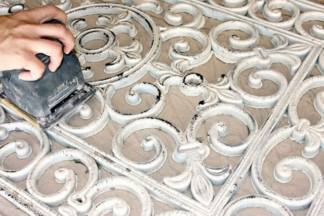Spray paint: rubber door mat with a primer (any light color), base coat with black (allow dry time between coats). Use two   coats of the Matte Heirloom White, allow a few days airing time outside. Use 120 grit   sand paper on a small hand sander, sand to distress/aged feel.