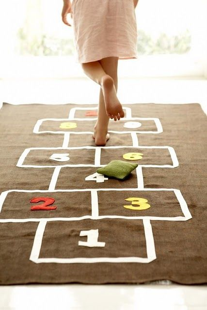 I was really good at hopscotch, were you?  Every day at recess we would rush out to the playground and play hopscotch.  We used rocks or coins to toss into the squares that you had to skip.  I like the idea of making a portable mat with the hopscotch outline on it so the kids can play it indoors or out.