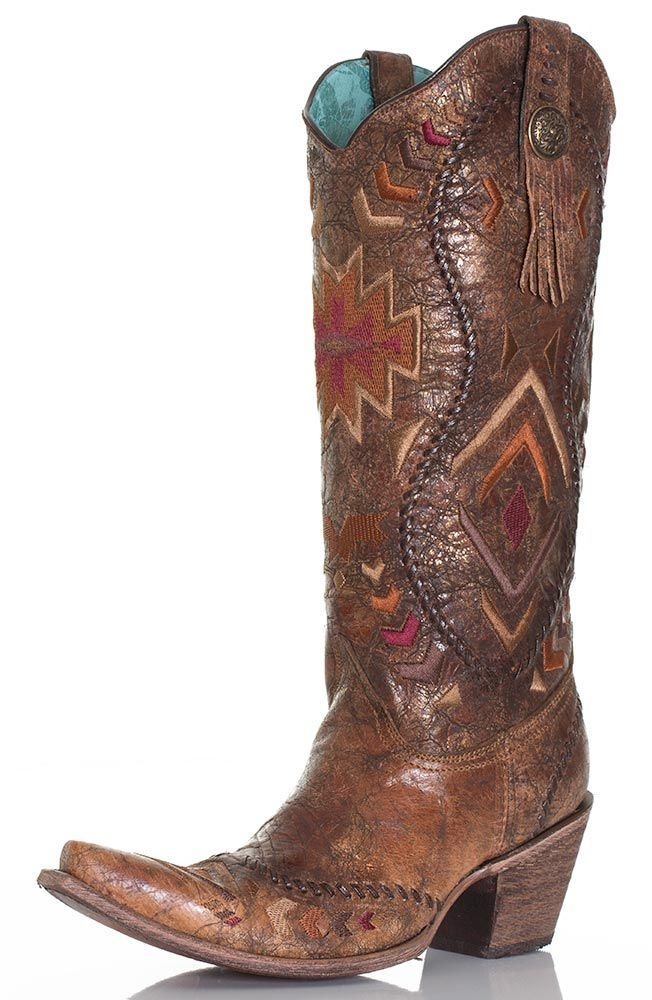 These tall top cowboy boots from Corral are stunning.  The cognac colored boots are perfectly distressed and well decorated with multicolored Aztec embroidery.  A look of copper metal makes them look extra luxurious.  Leather whipstitch details accent the top and swirl up the shaft.  Traditional pull straps have a not-so-traditional look with a metal concho accented with short fringe.  The pointed snip toe works well with the 3 inch fashion heel to add a vintage feel.  Make them a statement…
