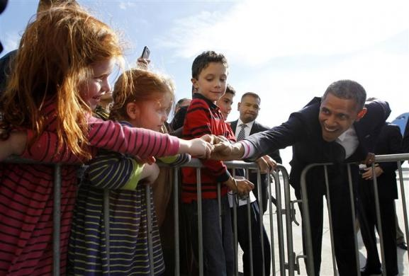 U.S. President Barack Obama reaches out to greet young girls upon his arrival at JFK Airport in New York, October 18, 2012. Obama is campaigning in New Hampshire on Thursday before attending a taping of the Daily Show with Jon Stewart and attending the 67th Annual Alfred E. Smith Memorial Foundation dinner in New York.  REUTERS-Jason Reed