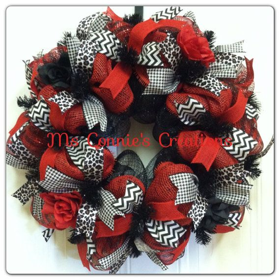 Red/black striped and solid black deco mesh with red paper mesh on 15 wreath frame. Completed wreath approximately 23. Four wired ribbons; animal print, houndstooth, black and white chevron, red burlap. Black and red roses.