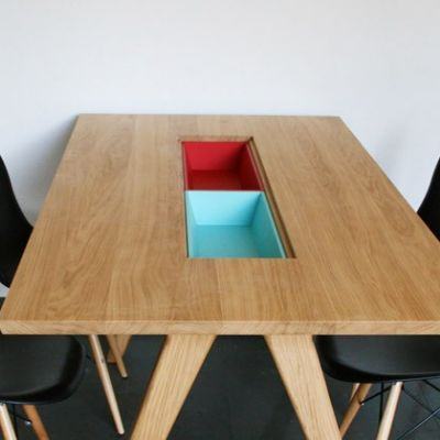 We've previously mentioned coffee tables with storage, but some dining tables have built-in storage, too. Extra space for stashing the tableware will often be welcome, but I'm also interested in such tables because many people use their dining tables as a workspace as well as a dining space and would