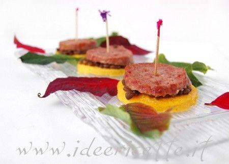 Primo piano presentazione crostini di polenta con lenticchie e cotechino