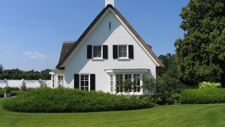 klassiek landhuis | een zeer royaal rietgedekt landhuis dat zowel licht en luchtig als klassiek van opzet is door de wit gekeimde gevels, witte erkers, witte omlijstingen en witte kozijnen met traditionele roedeverdeling en buitenluiken