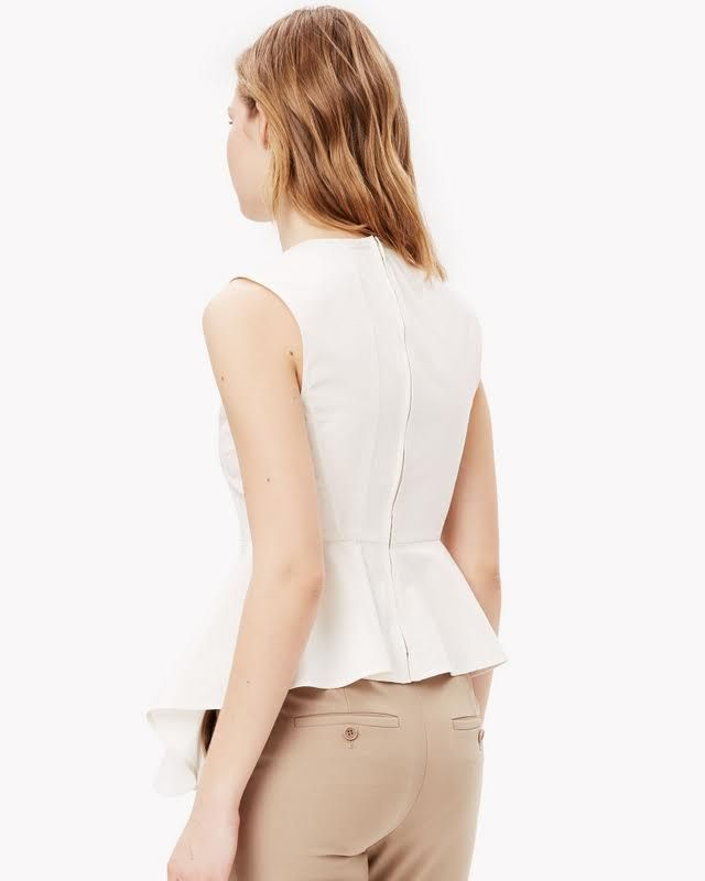 The sleeveless peplum top. Made from a crisp satin-finished poplin for that quintessential summery feeling, this innovative shirt features an exaggerated peplum front for an ultra-feminine statement. Dress it with cropped or wide pants for a directional look.