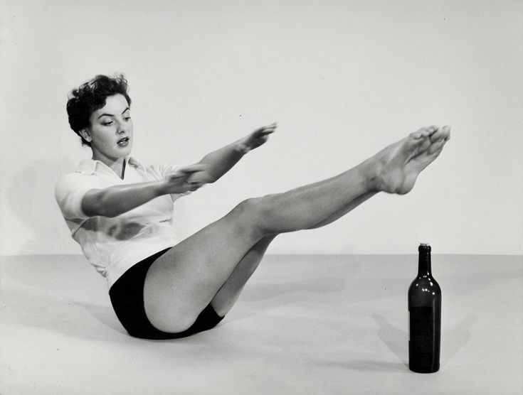 Gymnastiek, studio-opname. Vrouw strekt armen en benen tijdens grondoefening (voor de buikspieren) met wijnfles. Nederland, 1950-1960.