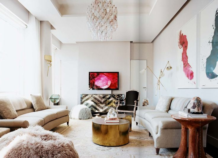 Contemporary Living Room Features James Nares Art Over Gray Linen Sofas Facing Each Other Across From Round Gold Coffee Tables As Well Flatscreen TV