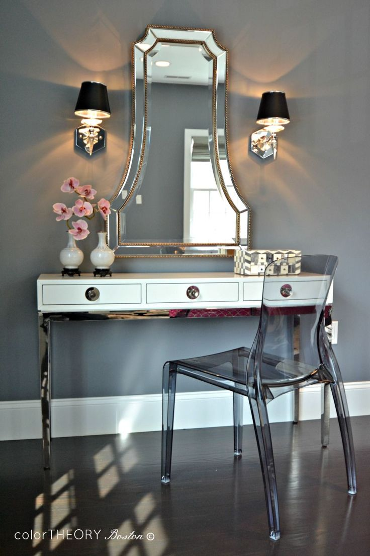 ... vanity with two drawers adorned with leather pulls topped with acrylic  makeup organizers and round silver mirror paired with an Ikea ghost chair,  ...