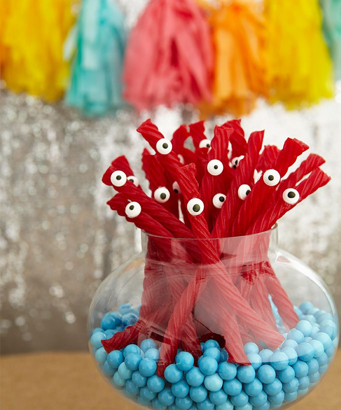 Muno Licorice: Red Vines accented with candy eyes (dots of icing made them stick) were placed in an apothecary jar lined with Sixlets candy. Source: Birthday Express
