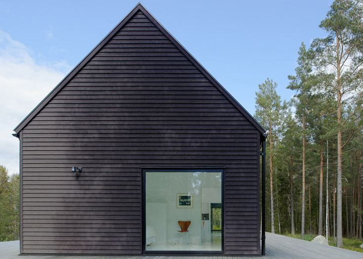 Small gabled house with black-painted pine walls by Erik Andersson Architects on Yxlan island in the Stockholm archipelago.