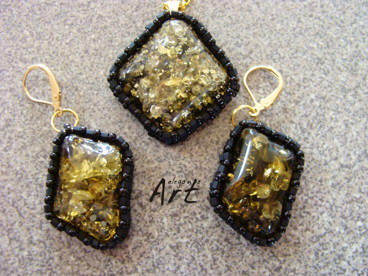 Elegancki komplet : wisior i kolczyki. Wykonane z połączenia czarnych koralików matowych i połyskujących. Imitacja bursztynu ładnie komponuje się  z prostym wzorem wykonanym z drobnych koralików. Wszystko wykończone pozłacanymi elementami.