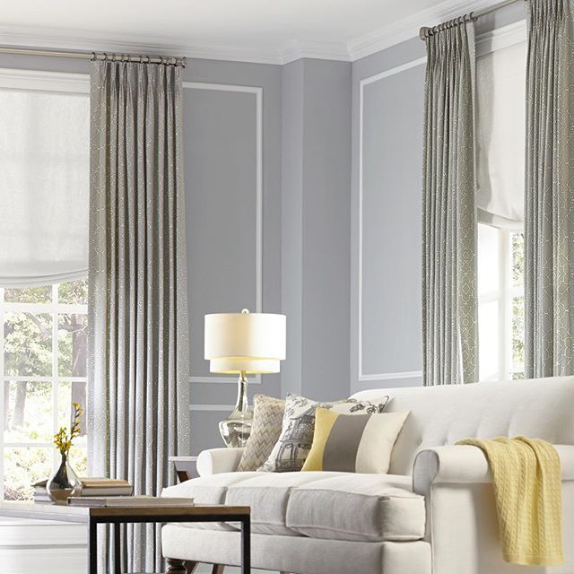 A trio of chevron, chinoiserie, and color block decorative throw pillows in shades of yellow, grey and cream gives this living room an easy, modern feel.  Shop custom window treatments and home accents by @loomdecor #NowOnDeringHall (link in bio).