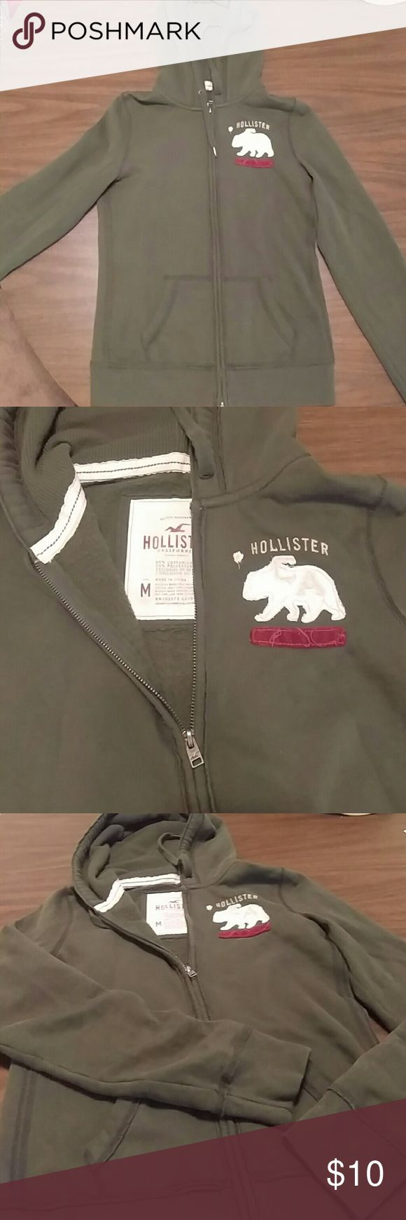 Hollister army green zip up hoodie Warm and soft zip up goody with bear applique on left chest. Good condition Hollister Tops Sweatshirts & Hoodies