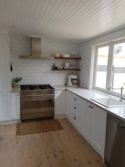 Classic White Kitchen. Shaker style doors. White Subway tile with grey grout. Wooden floating shelves. Grey iron bark shelves. Nordic Loft Caeserstone. Lime washed timber floors. V-joint ceiling. Bi-fold windows.90cm Smeg Oven. IKEA sink and tapware.