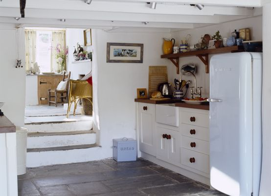 Country kichen- love the quirkiness of the split level with stps down into the kitchen, and of course my favourites: rough white walls, exposed beams and flagstone floor!