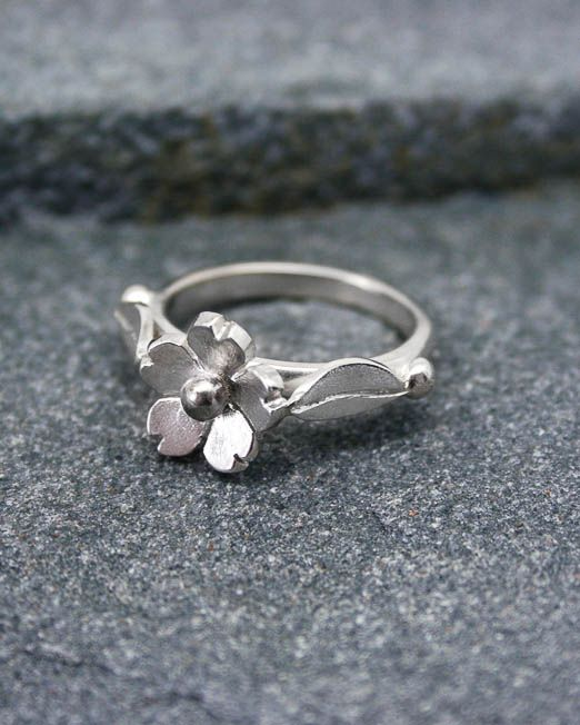 Sweet and simple daisy ring, this lovely ring is a must for everybody's jewellery box.  Suitable for any occasion.  The daisy has been hand saw pierced then lightly domed and completed with a silver bead to the centre with leaf shoulders.  The band is 2.2mm wide with a polished finish. The daisy measures 10mm. in diameter.
