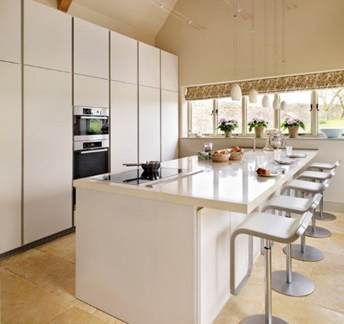 The natural tiles contrast with the white bulthaup b1 kitchen and metallic highlights of the Miele appliances and Lem stools.