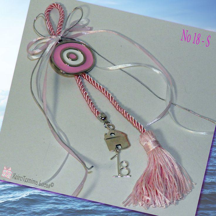 Ελληνικό, χειροποίητο γούρι για το 2018 σε αποχρώσεις του ροζ. Αποτελείται από ένα μεταλλικό μάτι σε ασημένιο χρώμα με ροζ και λευκό σμάλτο, δεμένο σε μία ροζ φούντα. Στην άκρη κρέμεται ένα σπίτι με την ημερομηνία του '18 για να πάει καλά η νέα χρονιά! Metal evil eye with pink enamel decorated with satin ribbons a metal little house a '18 date and a rose tassel as a good luck charm for 2018. Greek handmade christmas gift.