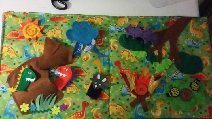 Felt dinosaur travel board with finger puppets, cave, Velcro Sun, button on fire and Bush