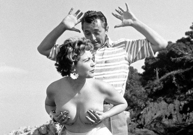 Simone Silva, un peu pompette, enlève le haut devant Robert Mitchum, hilare. Le cliché fait le tour du monde, le scandale est énorme. 1954