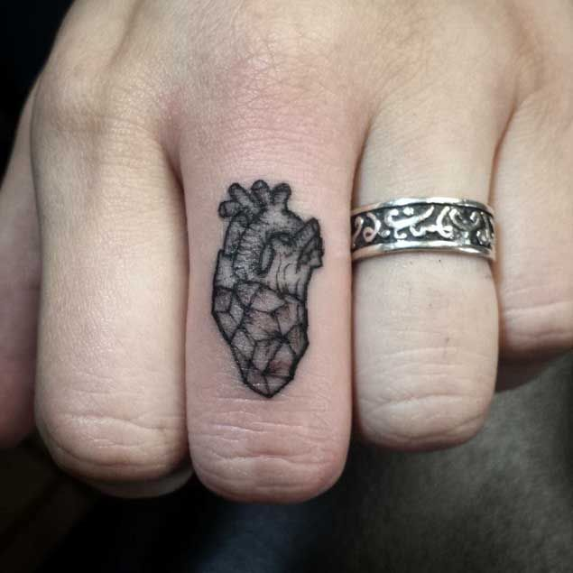 This tiny blackwork geometric heart tattoo is the perfect addition to this man's middle finger.