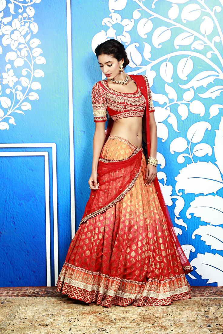 Presenting an exquisite shaded lehenga adorned with traditional embroidery. It has been paired with a fully embroidered red raw silk bandi and a net dupatta. It could also be teamed with a customised bandi instead of the choli. A stunning style perfect for the young, trendy and confident bride of today.